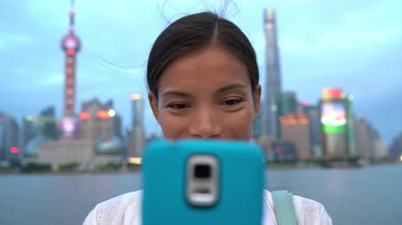 cabeçalho : Shanghai travel Asian girl tourist taking phone selfie photo on the Bund in Shanghai city vacation in China. Happy chinese young woman using smartphone app posting on social media. Multiracial person.