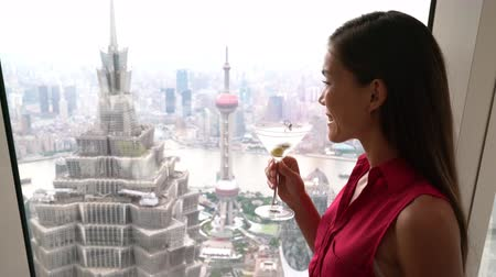 bebida alcoólica : Asian woman drinking martini alcoholic drink while looking at view of landmark skyscraper building in Lujiazui, Pudong, Shanghai city, China. Chinese tourist relaxing looking at window.