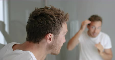 маслянистый : Man looking in bathroom mirror putting wax product touching his hair styling or checking for hair loss problem. Male problem of losing hairs.