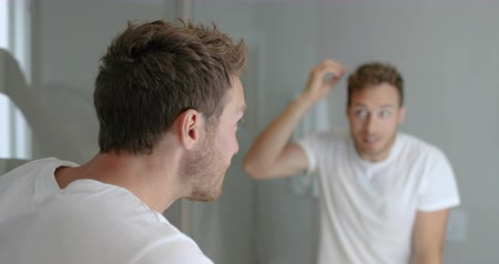 маслянистый : Hair loss man looking in bathroom mirror putting wax touching his hair styling or checking for hair loss problem. Male problem of losing hairs.
