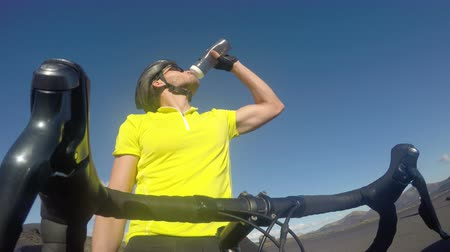 hidrasyon : Road bike cyclist man drinking water after cycling biking training, Healthy active lifestyle sports fitness man resting on bike after exercise. ACTION CAMERA.