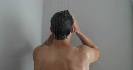 conditioner : Man in shower washing hair showering in bathroom at home. Unrecognizable person from behind rinsing shampoo and conditioner from hair in warm bath with modern bathroom. Stock Footage