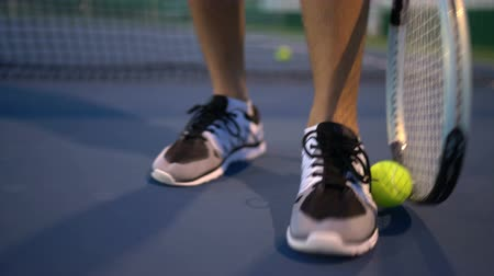 tennis player : Tennis. Tennis player playing tennis at night picking up tennis ball with racket. Stock Footage