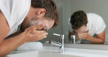 лицевой : Man washing face with facial cleanser face wash soap in bathroom sink at home. Стоковые видеозаписи