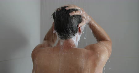 saç kremi : Shower man washing hair showering in bathroom at home. Unrecognizable person from behind rinsing shampoo and conditioner from hair in warm bath with modern bathroom.