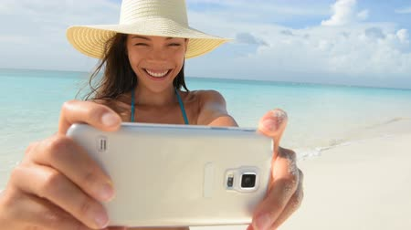 koupat se : Beach bikini girl taking selfie on phone with smartphone smiling happy. Mixed race Asian Caucasian woman self portrait photograph with mobile cell smart phone on summer travel holidays vacation.