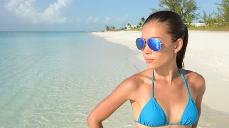 トレンディー : Beach bikini Asian woman wearing fashion sunglasses eye wear. Young female adult model with trendy blue mirrored aviator mirror sunglasses and turquoise swimwear top looking at the ocean. 動画素材
