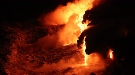 havaiano : Lava reaches ocean from lava stream on Big Island Hawaii. Lava running into pacific ocean and red hot glowing lava rocks flowing out with waves. Dramatic amazing nature landscape. Volcanic eruption.