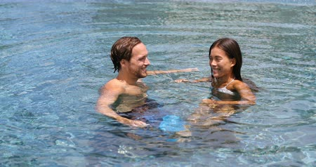 ırklararası : Honeymoon couple relaxing together in an infinity swimming pool in luxury resort spa retreat beach destination. Luxurious hotel travel vacation. People relaxed enjoying summer holidays. 59.94 FPS.