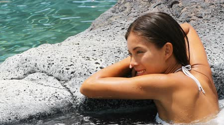 джакузи : Spa wellness - woman relaxing in hot tub whirlpool jacuzzi outdoor at luxury resort spa retreat. Happy young mixed race Asian Caucasian female model relaxed resting in water near pool on vacation.