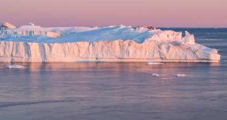 ilulissat : Arctic nature landscape with icebergs in Greenland icefjord with midnight sun sunset  sunrise in the horizon. Aerial drone footage video of ice. Ilulissat Icefjord with icebergs from glacier.