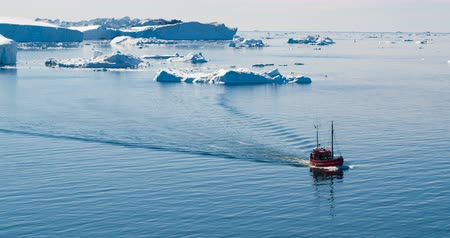disko bay : Icebergs and tourist fishing boat in Greenland iceberg landscape of Ilulissat icefjord with giant icebergs. Icebergs from melting glacier. Aerial drone video footage of arctic nature.