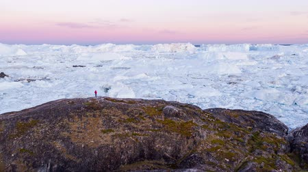 ilulissat : Travel wanderlust adventure in Arctic landscape nature with icebergs - tourist person looking at view of Greenland icefjord - aerial video. Man by ice and iceberg, Ilulissat Icefjord.