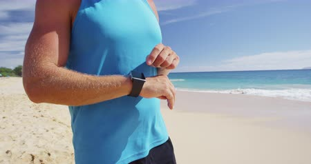 率 : Sports smartwatch - Athlete runner checking on fitness smartwatch exercising on beach. SLOW MOTION.