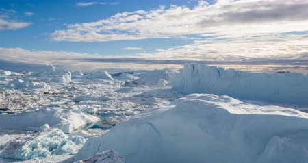 geleira : Iceberg aerial footage - giant icebergs in Disko Bay on greenland floating in Ilulissat icefjord from melting glacier Sermeq Kujalleq Glacier, aka Jakobhavns Glacier. Global warming and climate change Stock Footage