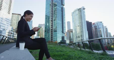 Ванкувер : Businesswoman using smart phone in the city. Young woman professional in a big city using smartphone. Vancouver, Canada, Shot on RED. Стоковые видеозаписи