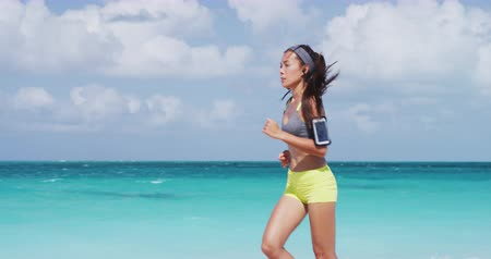 biustonosz : Determined young runner jogging on sea shore. Sporty female is listening music through headphones against sky. Woman in sportswear exercising at beach during sunny day.