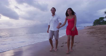 felnőtt : Honeymoon passionate couple holding hands walking on beach. Romantic Newlywed happy young couple enjoying ocean sunset during travel vacation getaway freedom joy.