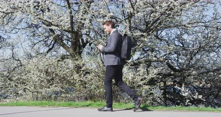 floração : Smiling businessman using mobile phone by flowering tree. Male professional is walkingin city park. Business man in formalwear smart casual suit on during sunny day.