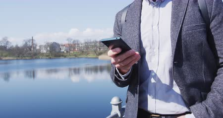 bolso : Businessman using smartphone in formals suit jacket. Male professional using mobile cell phone app standing by lake in city park. Business man in city during sunny day. SLOW MOTION shot on RED.