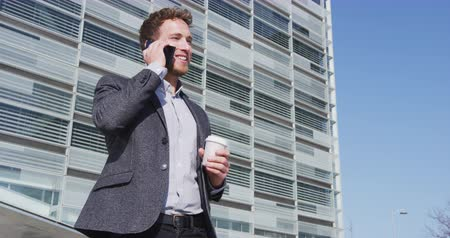 felnőtt : Smiling male professional talking on smartphone while having coffee. Businessman is holding disposable cup while standing against building. He is wearing formals at city during sunny day.