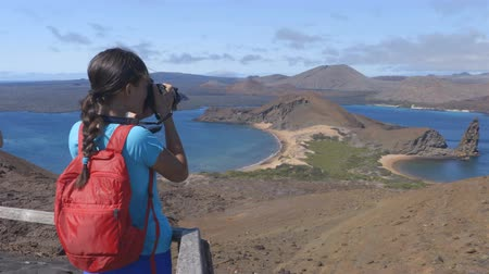 ecuador : Galapagos tourist taking photos enjoying famous inconic view on Bartolome Island. Travel vacation adventure woman taking photos using camara at viewpoint and visitor site of landscape of Pinnacle Rock