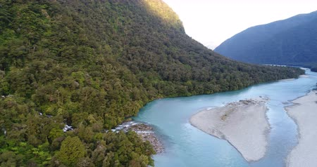 к юго западу : New Zealand nature landscape aerial drone video of Haast River and Roaring Billy Falls waterfall in Mount Aspiring National Park, South Island, New Zealand. Стоковые видеозаписи