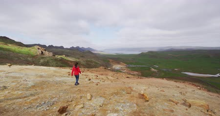 seltun : Iceland nature video of tourist walking by volcano geothermal fields with volcanic activity of fumaroles. Seltun geothermal field in Krysuvik, Reykjanes peninsula, Iceland