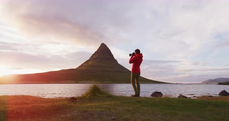fotoğraflar : Travel nature photographer tourist taking photo using camera on Iceland. Kirkjufell mountain landscape on West Iceland. Iceland tourist destination and icon.
