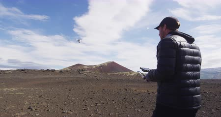 gibi : Drone pilot operator flying steering UAV drone as hobby filming shooting video or taking photos on travel in amazing nature landscape on Iceland Stok Video