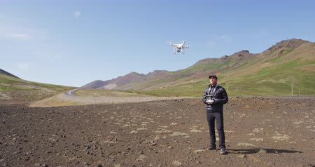 unmanned aircraft : Drone pilot operator flying drone as hobby filming shooting video or taking photos on travel in amazing nature landscape on Iceland