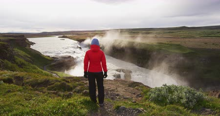 gullfoss : Waterfall Gullfoss on Iceland in Icelandic nature. Tourist looking at Gullfoss aka Golden Falls is a famous tourist attraction and landmark destination on Iceland on the Golden Circle, Stock Footage