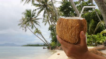 saman : Coconut water on paradise beach - vacation woman drinking coconut. Closeup of fresh tropical coconut fruit for healthy organic snack during summer holidays.