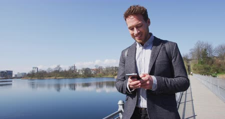 İskandinavya : Smartphone - Young urban professional business man using phone walking in city Park. Businessman in 30s using smartphone app in Copenhagen, Denmark, Scandinavia