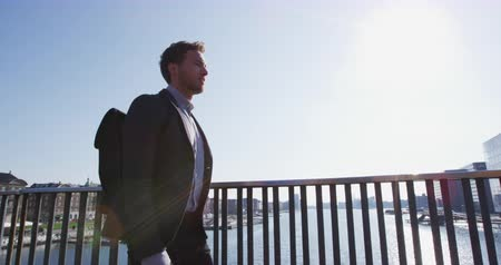 casual wear businessman : Young urban professional business man walking to work wearing backpack wearing backpack. Businessman in 30s in Copenhagen, Denmark, Scandinavia. Stock Footage