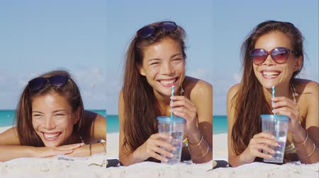 lefekvés : Vertical Video of Woman drinking water on beach smiling and laughing looking at camera. Girl on beach vacation in bikini sun tanning relaxing on beach holiday