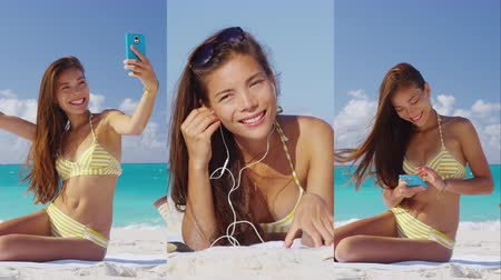 купальный костюм : Woman using smartphone app on beach taking selfie, listening to music. Vertical videos of bikini girl looking at cell phone relaxing on vacation travel. under the tropical sun.