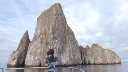 ecuador : Galapagos Cruise ship tourist on boat looking at Kicker Rock nature landscape. Iconic landmark and tourist destination for birdwatching, diving and snorkeling, San Cristobal Island, Galapagos Islands.