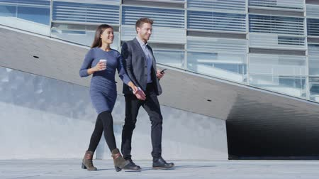 jovem : Business people walking and talking - business woman and business man outside by office building. Young urban professional businesswoman and businessman in 30s in smart casual clothing. SLOW MOTION. Stock Footage
