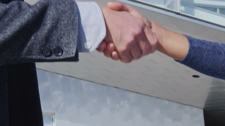 casual wear businessman : Business Handshake - business people shaking hands. Handshake between business man and woman outdoors by business building. Casual wear, young people in their 30s. shaking hands close up. SLOW MOTION