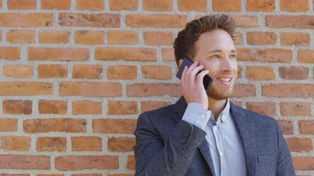 casual wear businessman : Businessman talking business on phone holding smartphone in city street in smart casual wear standing against brick wall urban background. Happy caucasian business man. Stock Footage