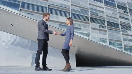 parceria : Business Handshake - business people meeting shaking hands. Handshake between business man and woman outdoors by office building. Casual clothing, young people, 30s. shaking hands closeup. SLOW MOTION Vídeos