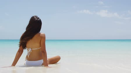 купальный костюм : Travel vacation girl in white bikini relaxing on tropical beach sun tanning in summertime.Woman in relaxation mode at idyllic stunning tropical luxury resort hotel. SLOW MOTION.