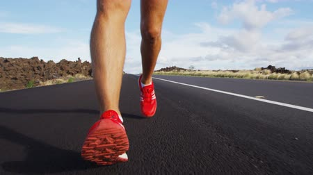 buty sportowe : Running shoes on male triathlete runner - close up of feet running on road. Man jogging outside exercising training for triathlon ironman
