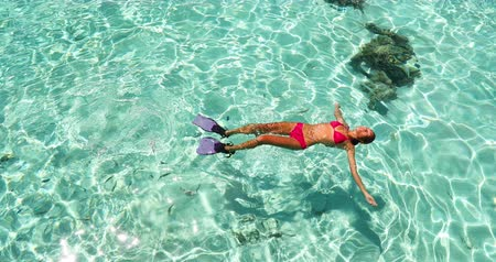 genç kız : Vacation travel - woman swimming in clear pristine water relaxing on her back wearing red bikini and pink snorkeling fins. Beautiful beach reef lagoon top view.