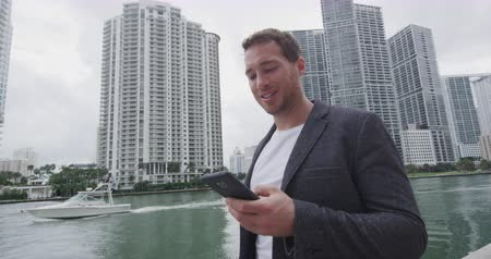 небоскреб : Phone app - Happy young man businessman portrait using phone. Smiling confident business man using cell smartphone app in Miami. City lifestyle people in Miami, Florida USA