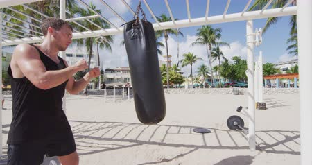 sportowiec : Boxing fitness man training boxing punching bag working out muscles using boxing heavy bag at outdoor public gym on South Beach, Miami, Florida, USA