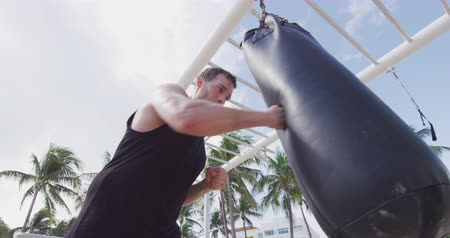 batoh : Fitness man training boxing punching heavy bag outside in outdoor gym. Man using boxing heavy bag at outdoor public gym.