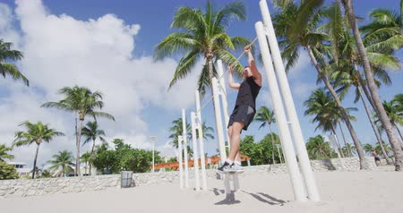 bodyweight : Fitness man doing pull ups chest to bar training working out muscles at outdoor gym on South Beach, Calisthenic Park South Beach, Miami, Florida. SLOW MOTION shot on RED EPIC.