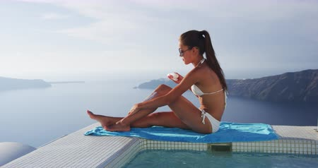 stehno : Sunscreen suntan bikini woman applying sunscreen spf lotion on leg and body spreading sunblock cream on legs on summer travel vacation. Luxury travel destination, pool and amazing view, Santorini.